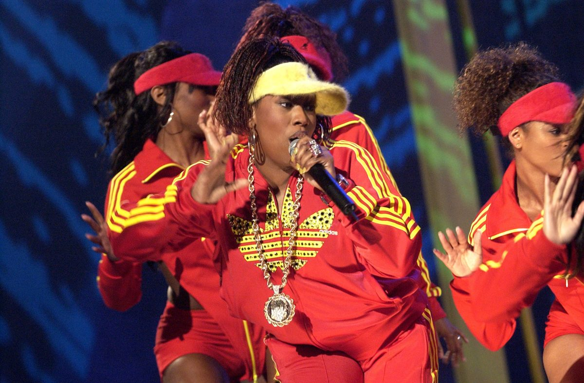 Missy Elliott wearing a red and yellow tracksuit with a yellow visor.