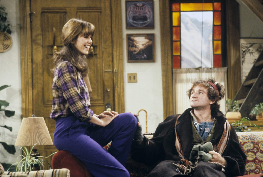 (L-R) Pam Dawber and Robin Williams sitting on a couch on 'Mork & Mindy'