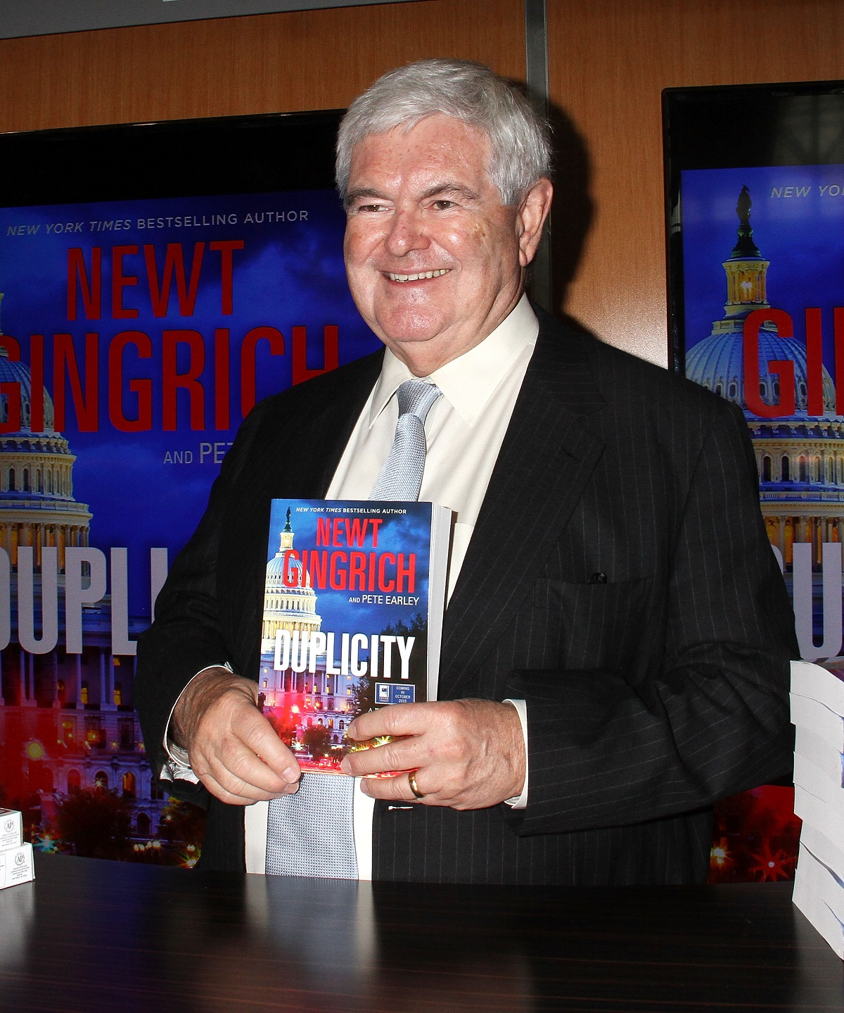 Newt Gingrich holding his book 'Duplicity' in 2015