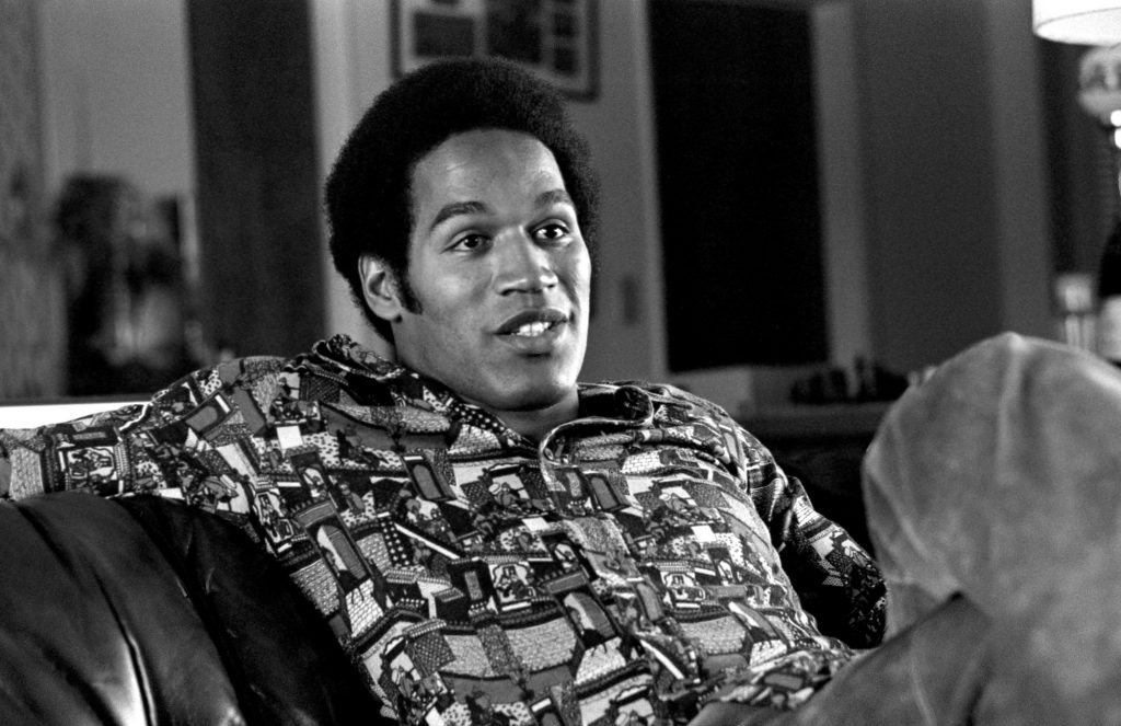 O.J. Simpson sitting on a couch, talking, in black and white
