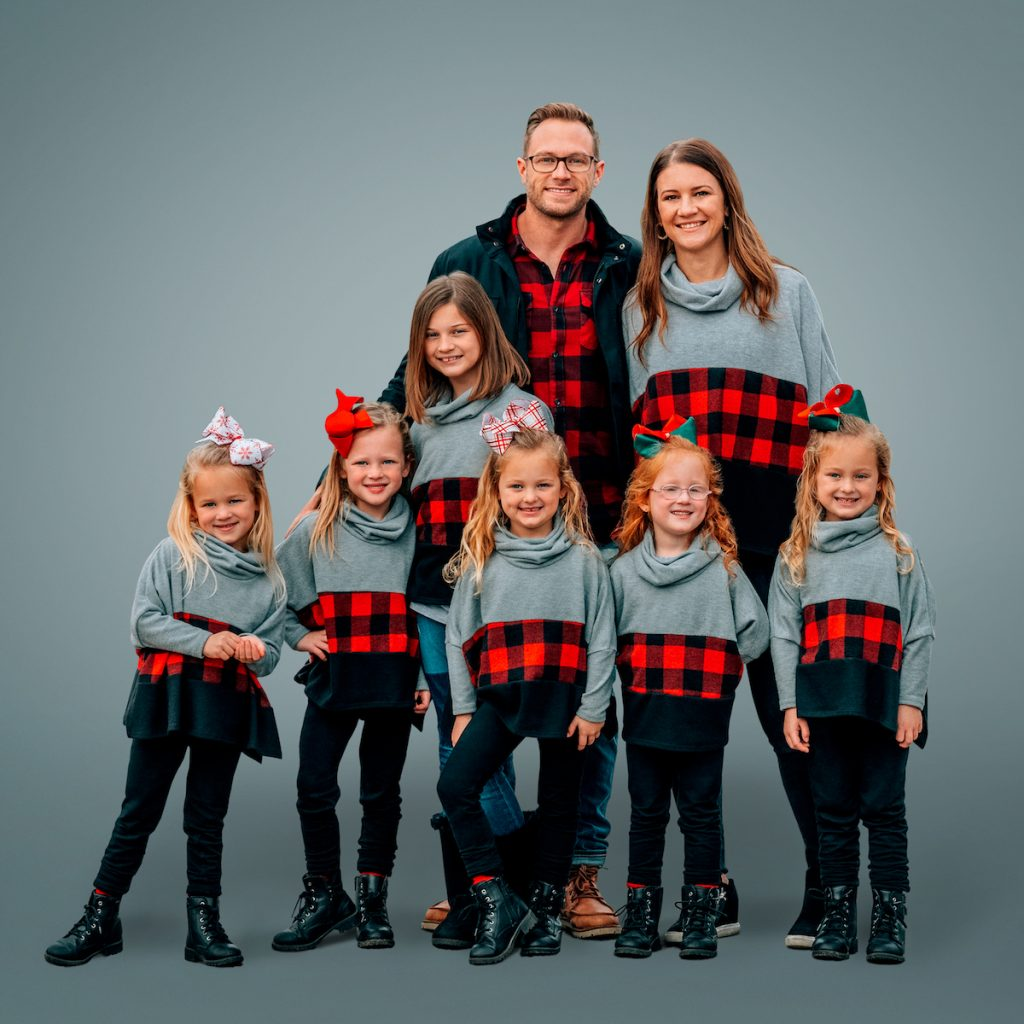 Portrait of Adam Busby and Danielle Busby with Blayke and the Busby quints from 'OutDaughtered' on gray background.