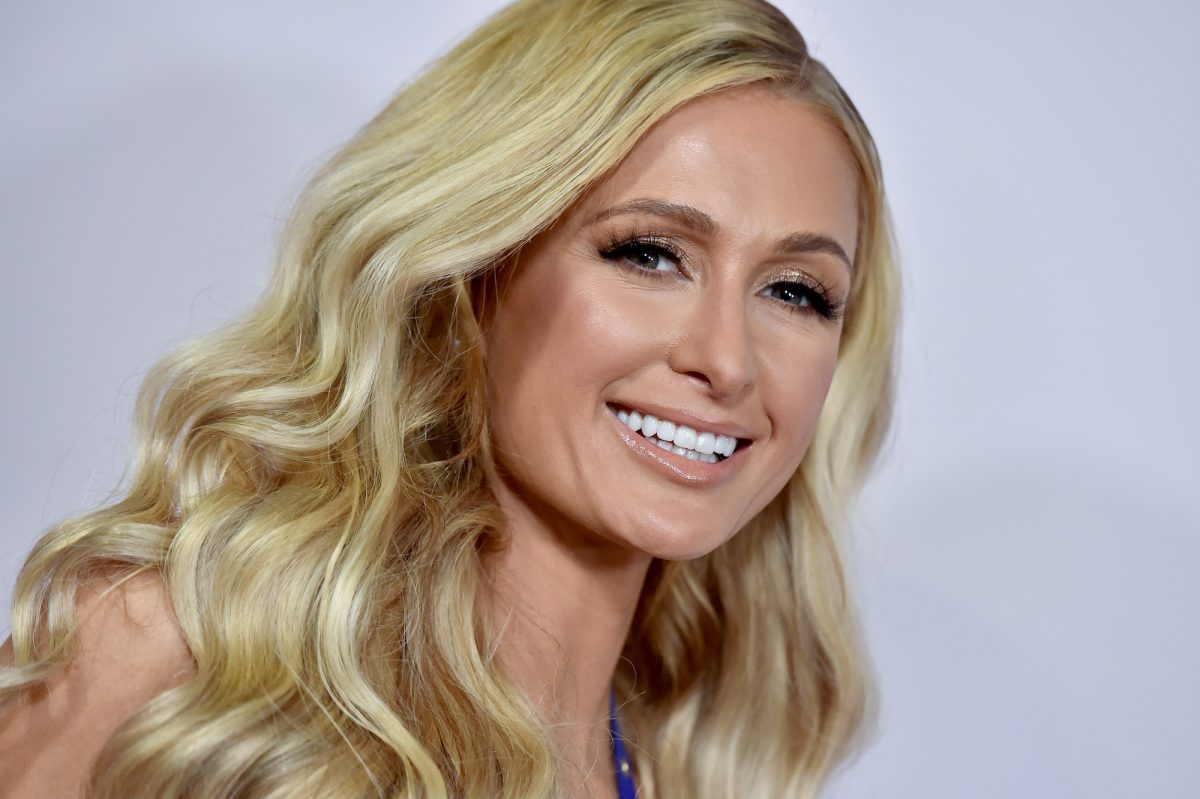 Paris Hilton smiling in front of a white background