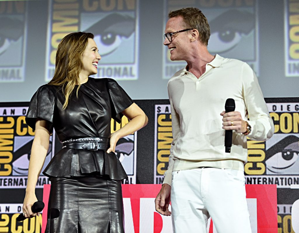 Elizabeth Olsen and Paul Bettany smile at each other at the San Diego Comic-Con International 2019 Marvel Studios Panel