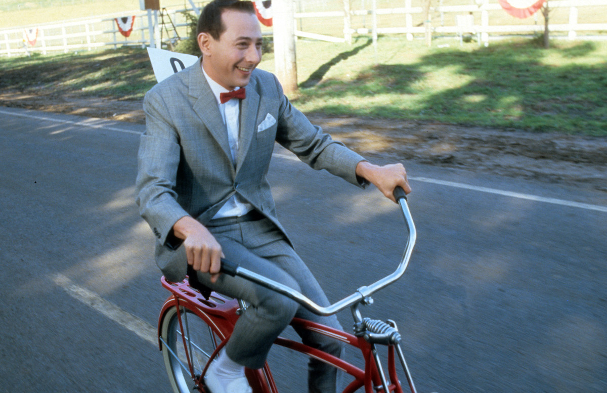 Paul Reubens rides a bike in a scene from the film 'Pee-Wee's Big Adventure'