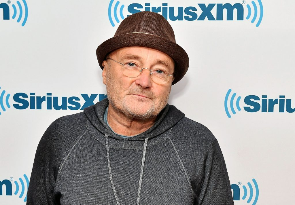 Phil Collins smiling in front of a white background