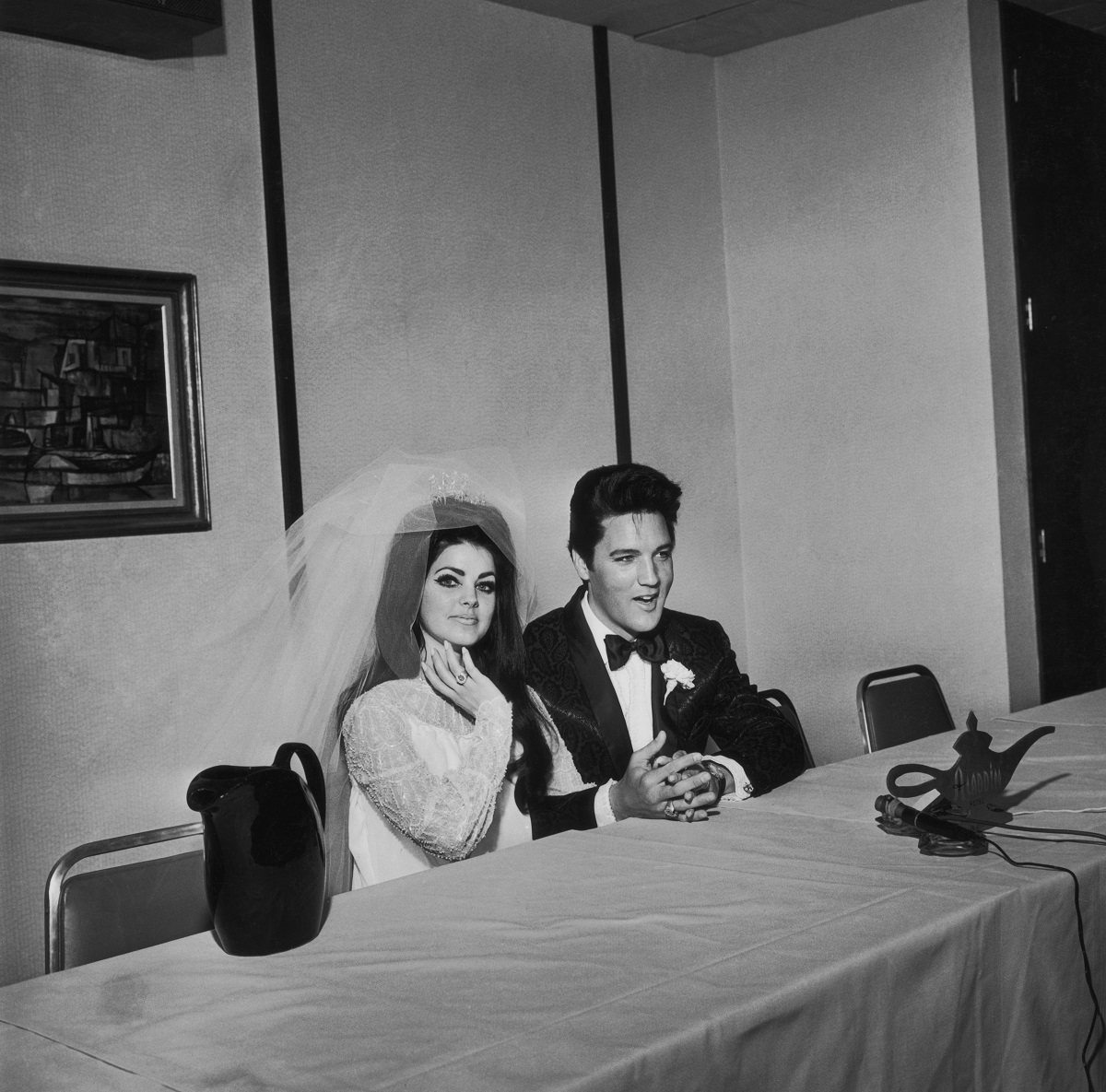 Priscilla and Elvis Presley seated at a table on their wedding day at the Aladdin Hotel in Las Vegas in 1967