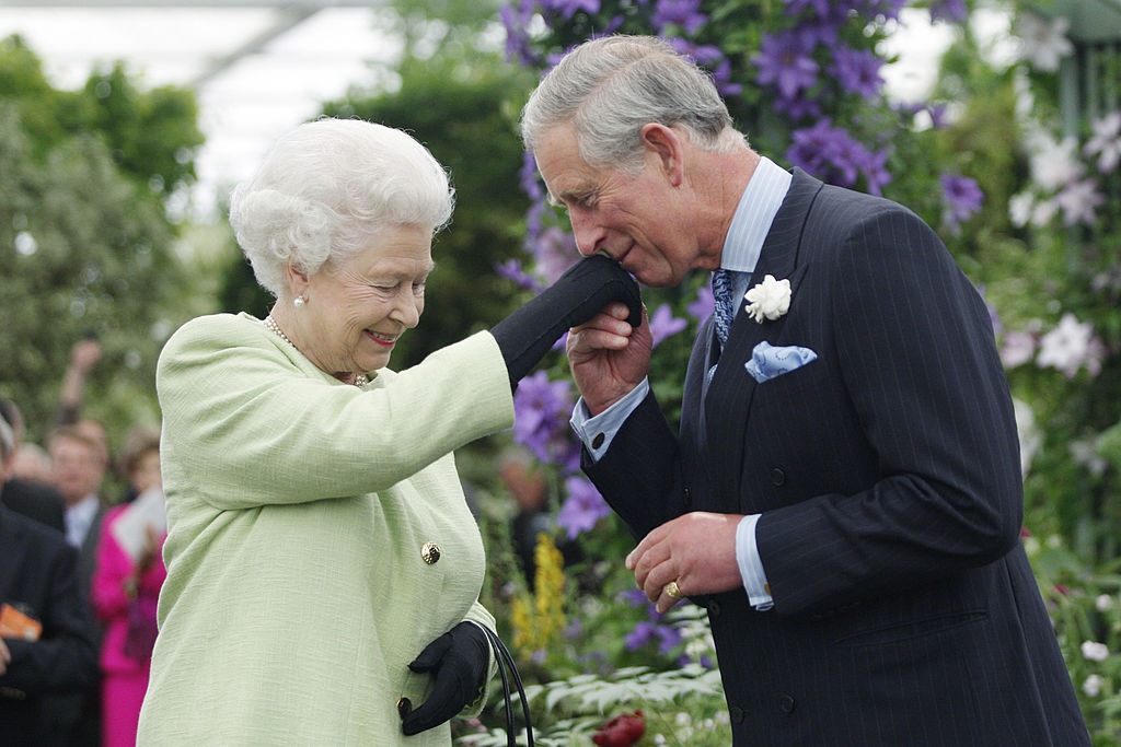 Prince Charles air kissing Queen Elizabeth's hand
