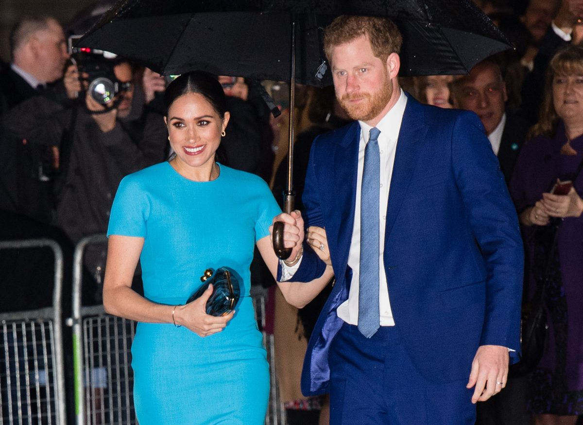 Prince Harry and Meghan Markle stand in the rain under an umbrella outside The Endeavour Fund Awards at Mansion House