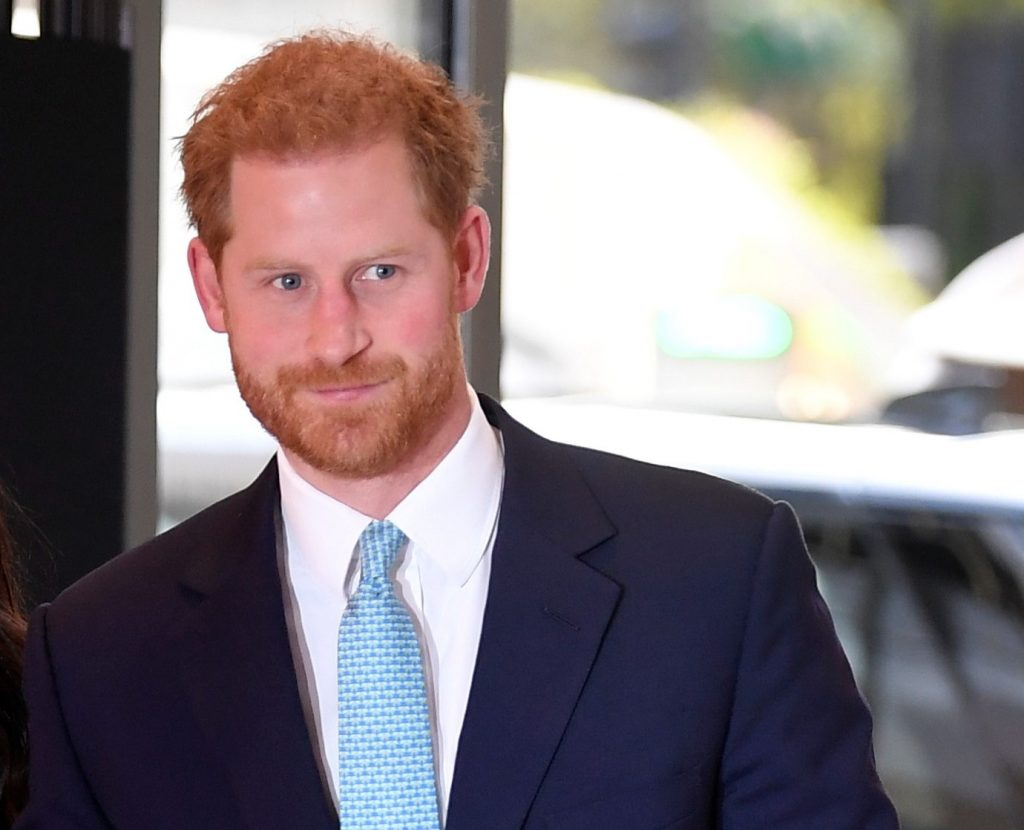 Prince Harry smiles slightly walking into building