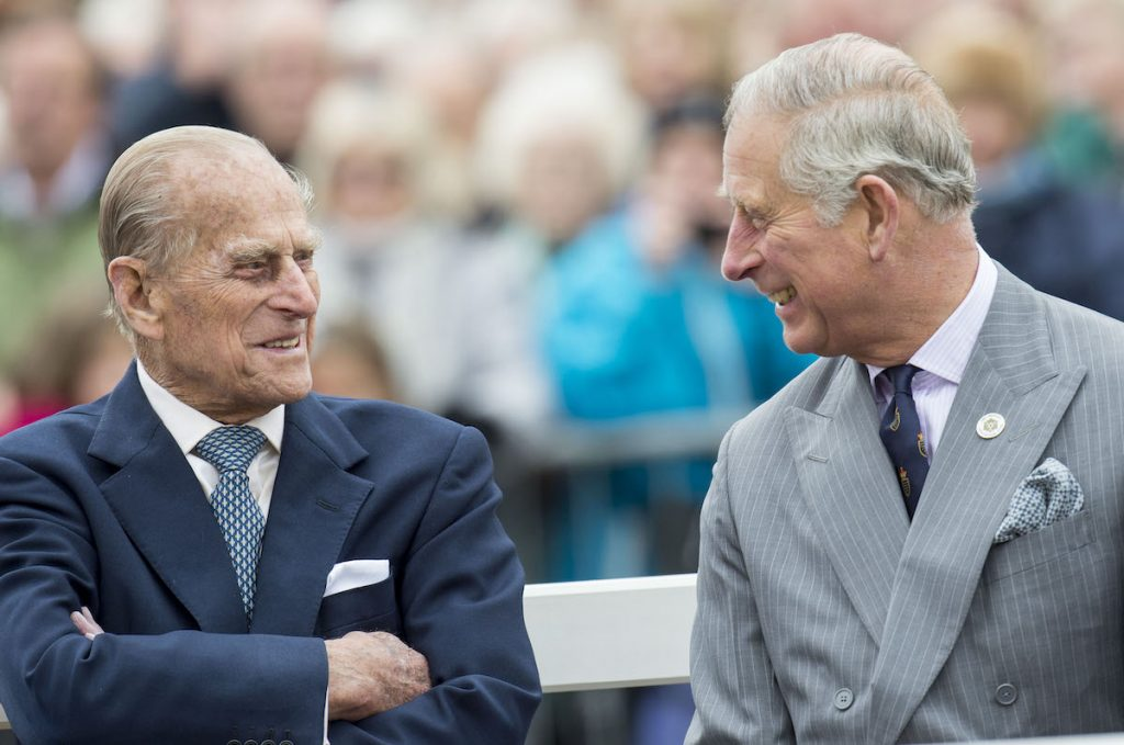 Prince Philip, and Prince Charles smiling at each other