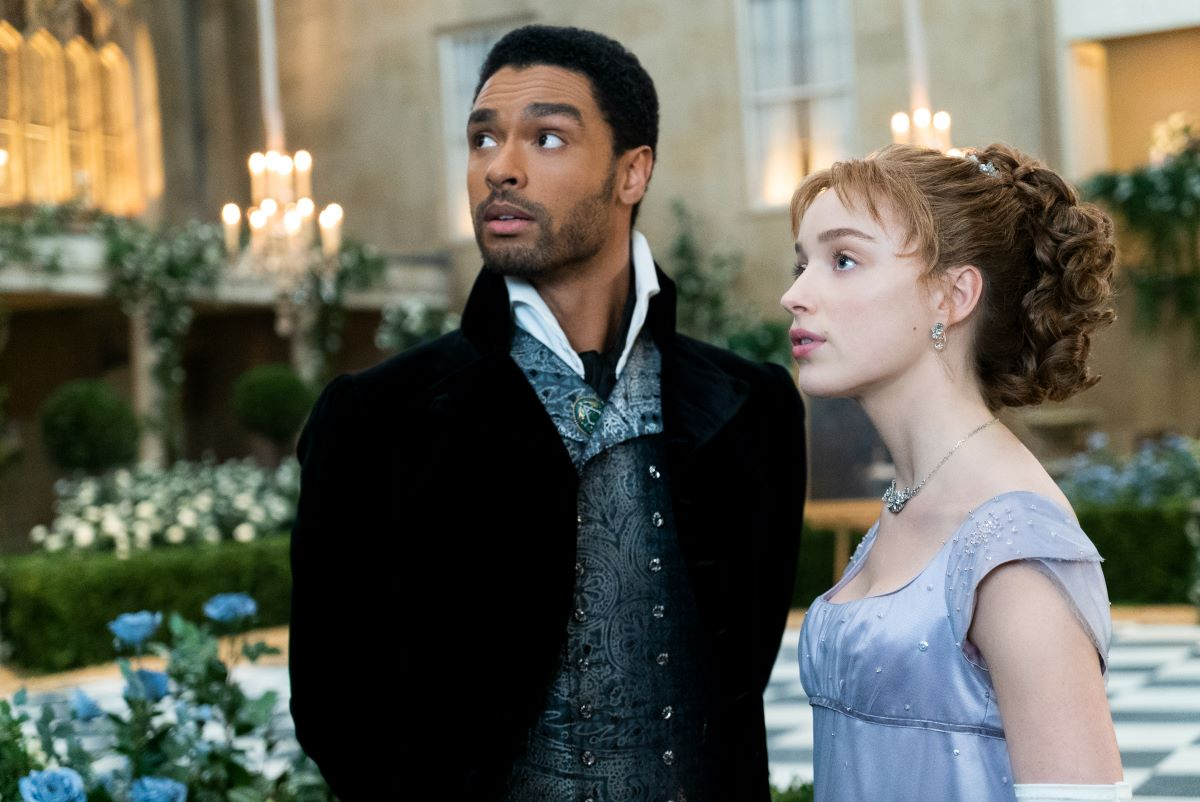 Regé-Jean Page and Phoebe Dynevor stand together in costume on 'Bridgerton'