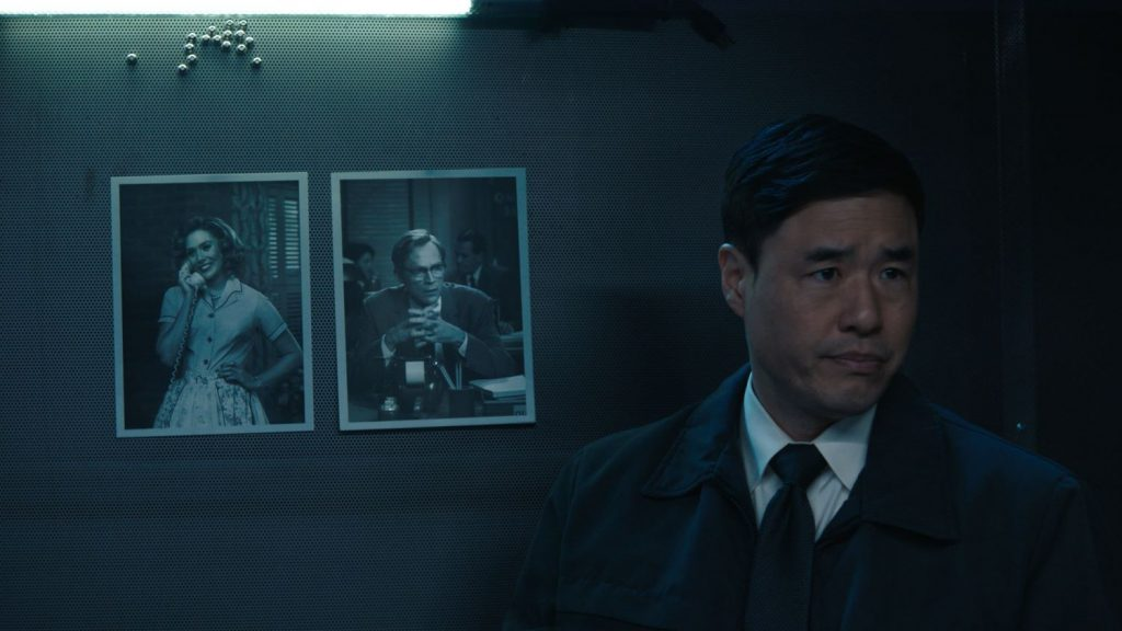 Randall Park in standing in front of photos of Wanda and Vision in 'WandaVision'