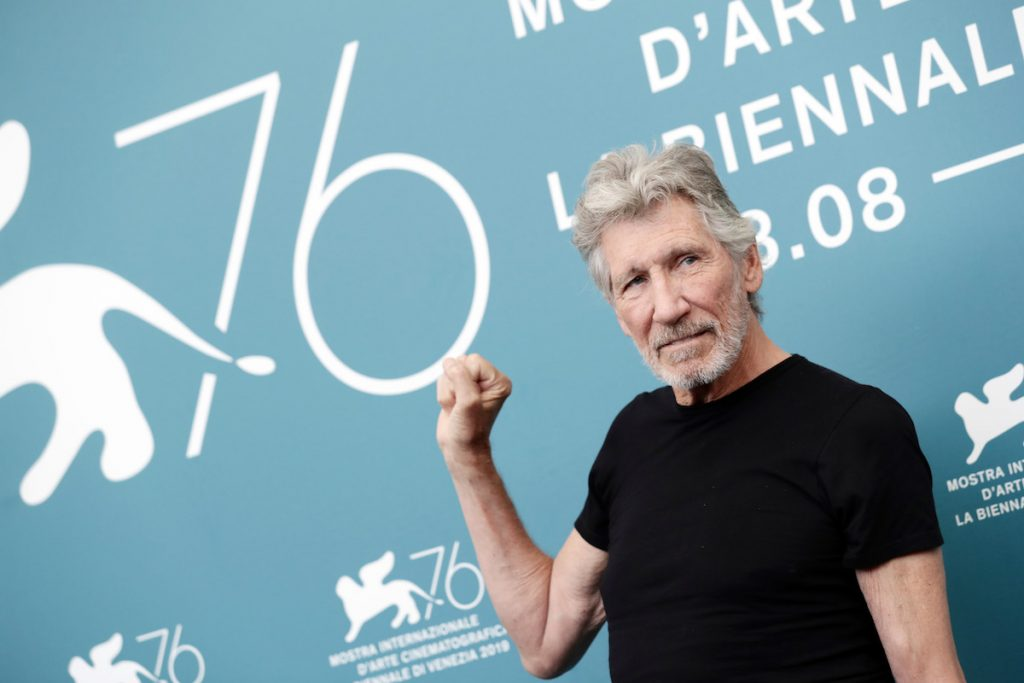 Roger Waters photo of his upper body wearing a black t-shirt and holding up his right hand.