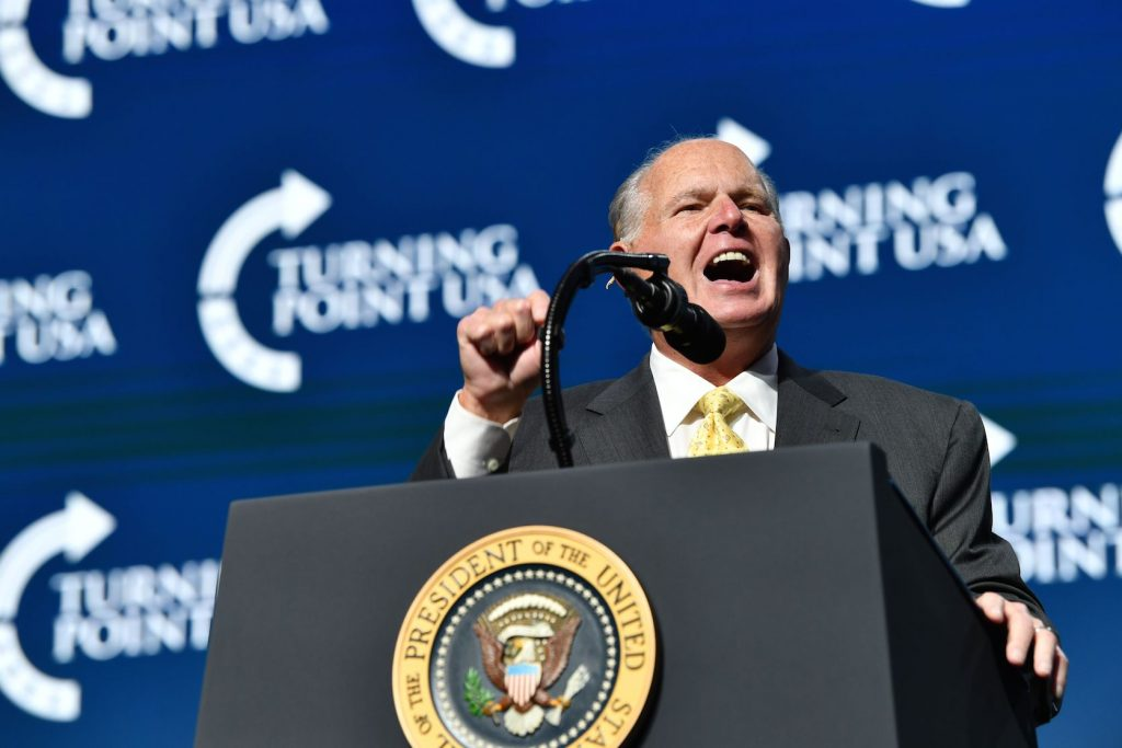 Rush Limbaugh shouting into a microphone at a summit