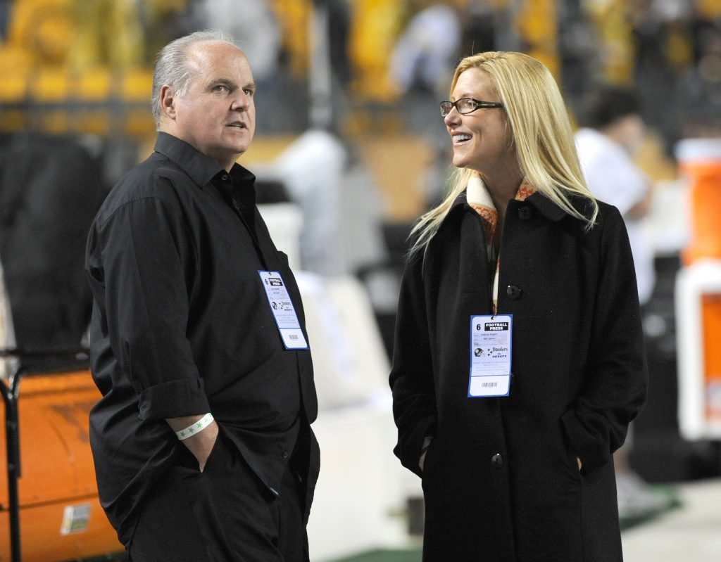 Rush Limbaugh (L) and his wife, Kathryn Adams Limbaugh, standing on the sidelines of a football game