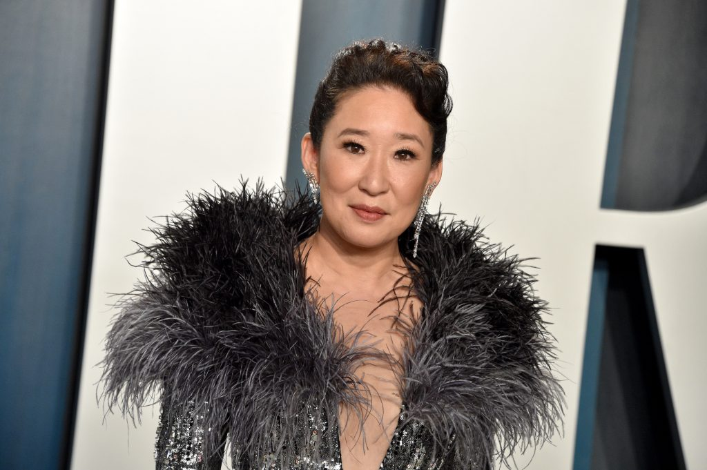 Sandra Oh smiling in front of a blue and white background