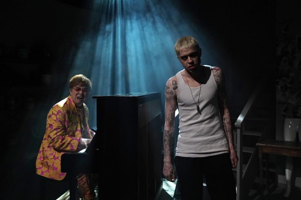 "Bowen Yang as Elton John plays piano and Pete Davidson as Stu stands in front of him performing during the ""Stu"" sketch on 'Saturday Night Live'"