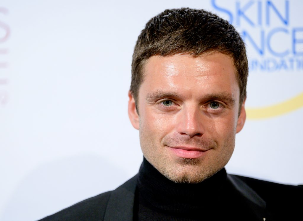 Sebastian Stan smiling in front of a white background