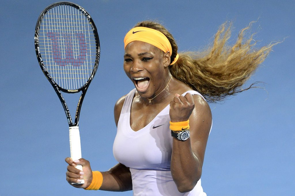 Serena Williams on the tennis court wearing white, a yellow headband and holding a tennis racket in her right hand.