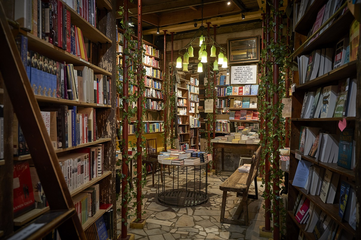 The interior of the Shakespeare and Company Bookshop in Paris in 2020. The wooden bookshelves are packed with books, and leaf-wrapped ladders help customers reach the tops of the shelves.