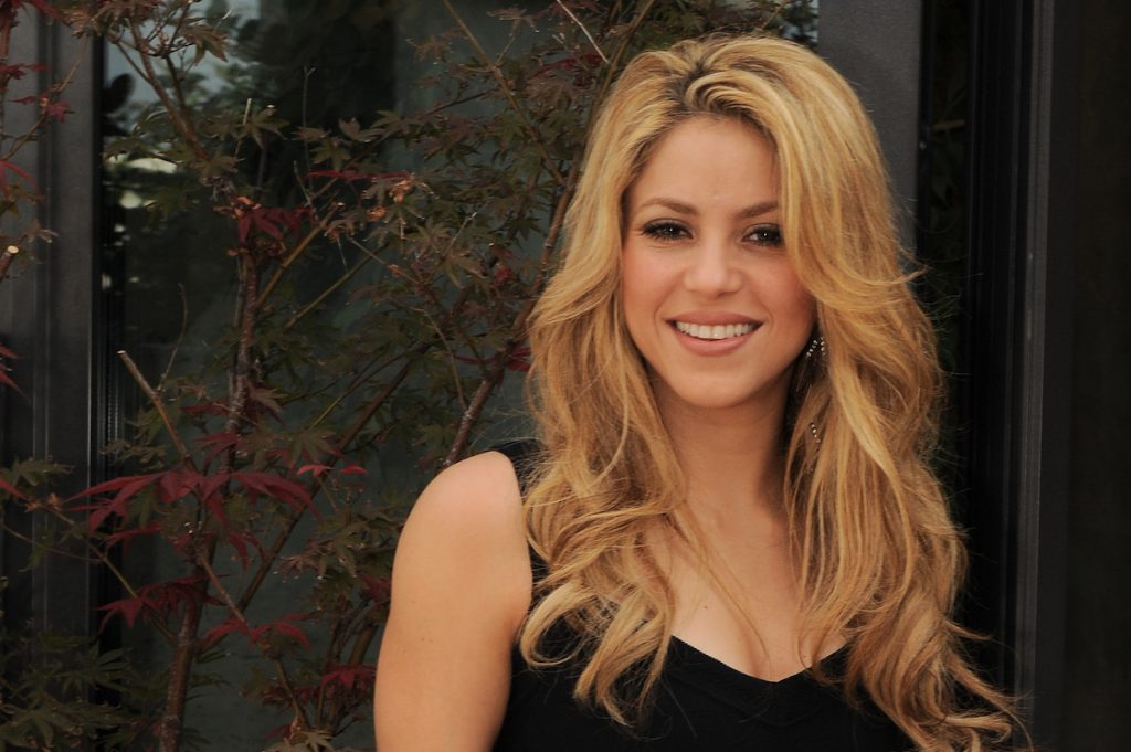 Shakira smiling at the camera with her hair down, wearing a black tank top.