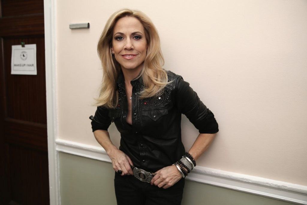 Sheryl Crow wearing black and leaning against a wall.