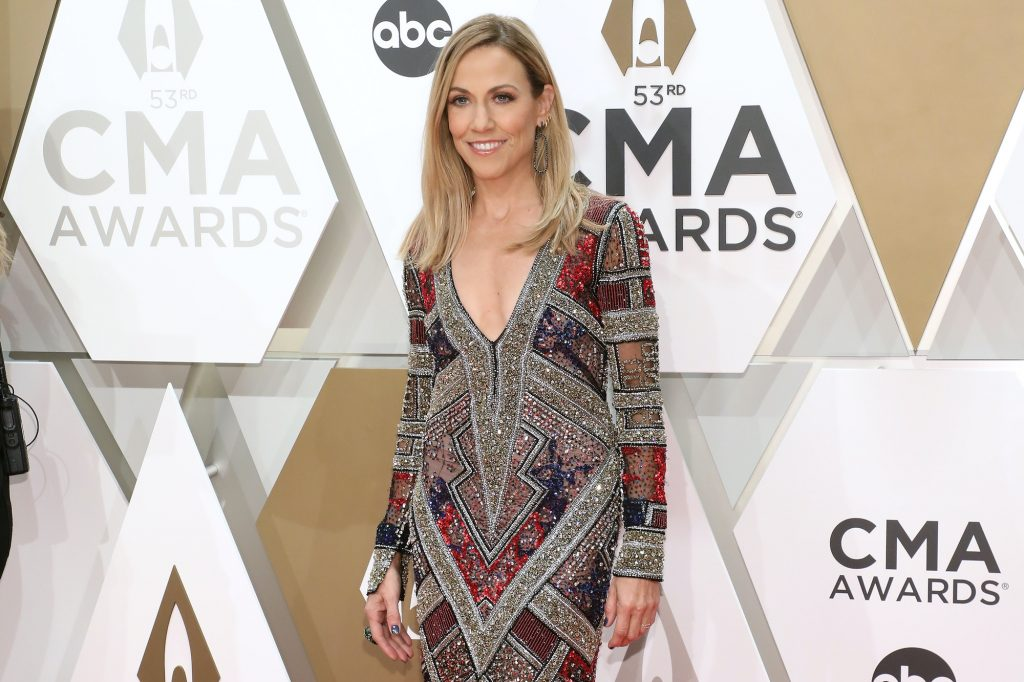 Sheryl Crow smiling in front of a tan and white background