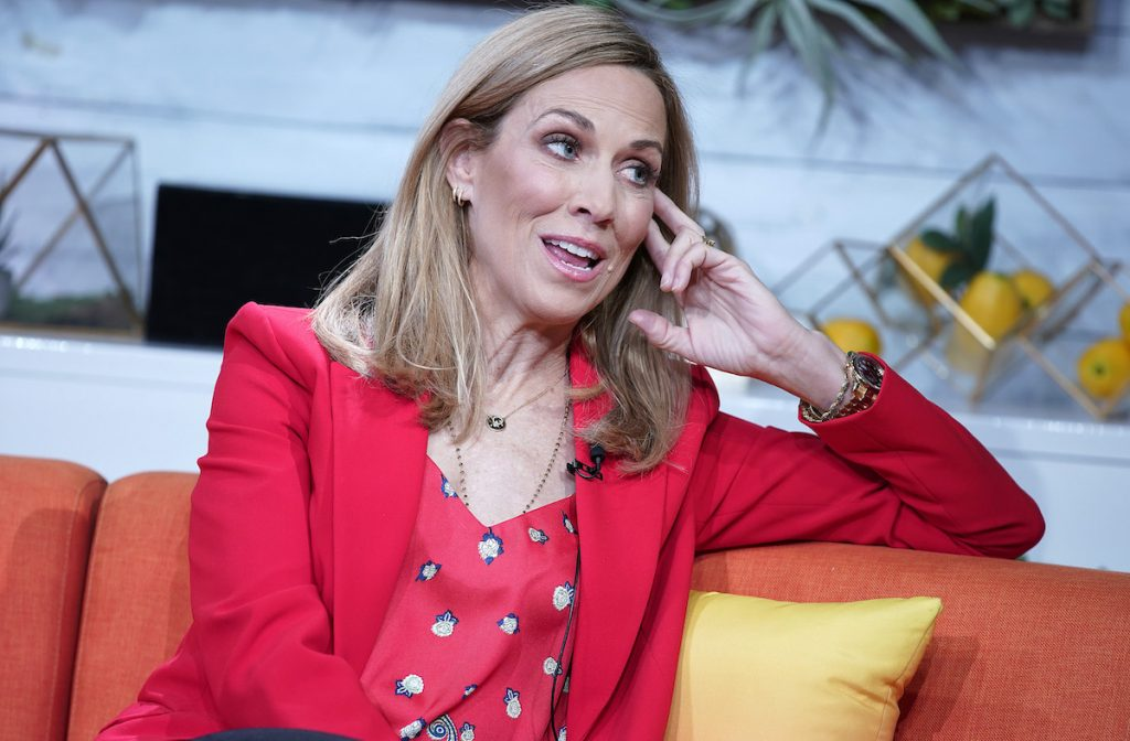 """Singer Sheryl Crow, dressed in a bright-red blazer, visits BuzzFeed's """"AM to DM"""" on March 5, 2020, in New York City."""