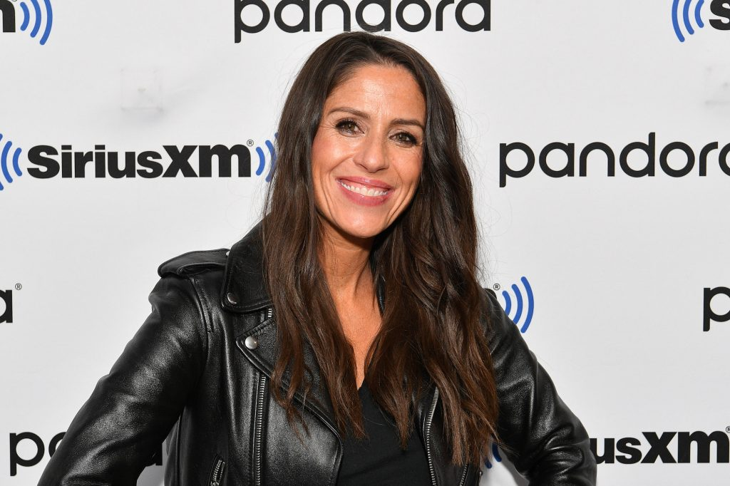 Soleil Moon Frye smiling in front of a white background with repeating logos