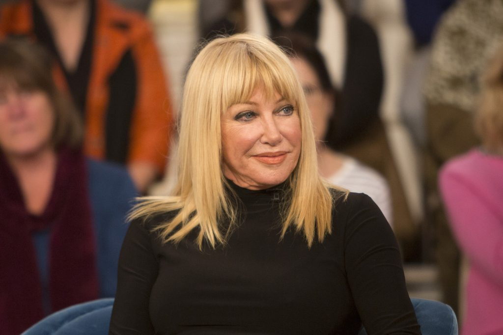 Suzanne Somers smiling, seated in front of a blurred audience