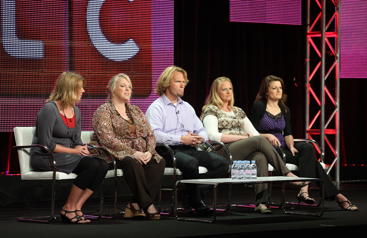 Kody Brown and his four wives sitting on stage at a TCA panel in 2010 in front of a TLC logo