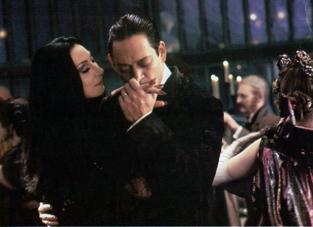 Anjelica Huston is kissed on the hand by Raul Julia in a scene from the film 'The Addams Family'