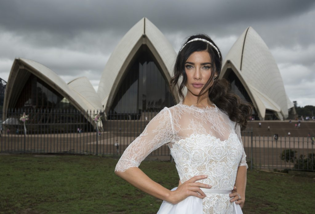 Jacqueline MacInnes Wood smiling in a wedding dress, in front of the Sydney Opera House