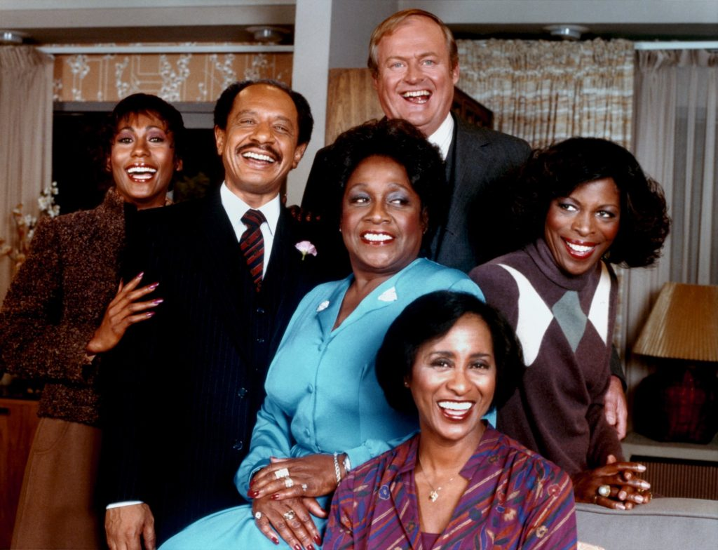(L-R) Berlinda Tolbert, Sherman Hemsley, Isabel Sanford, Franklin Cover, Roxie Roker, and Marla Gibbs (seated) smiling and laughing