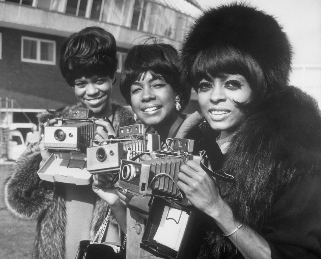 The Supremes, Florence Ballard, Mary Wilson, and Diana Ross pose with their cameras as they arrive at London Airport