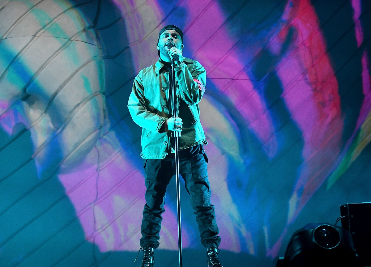 The Weeknd performing on stage with a microphone at Coachella in 2018
