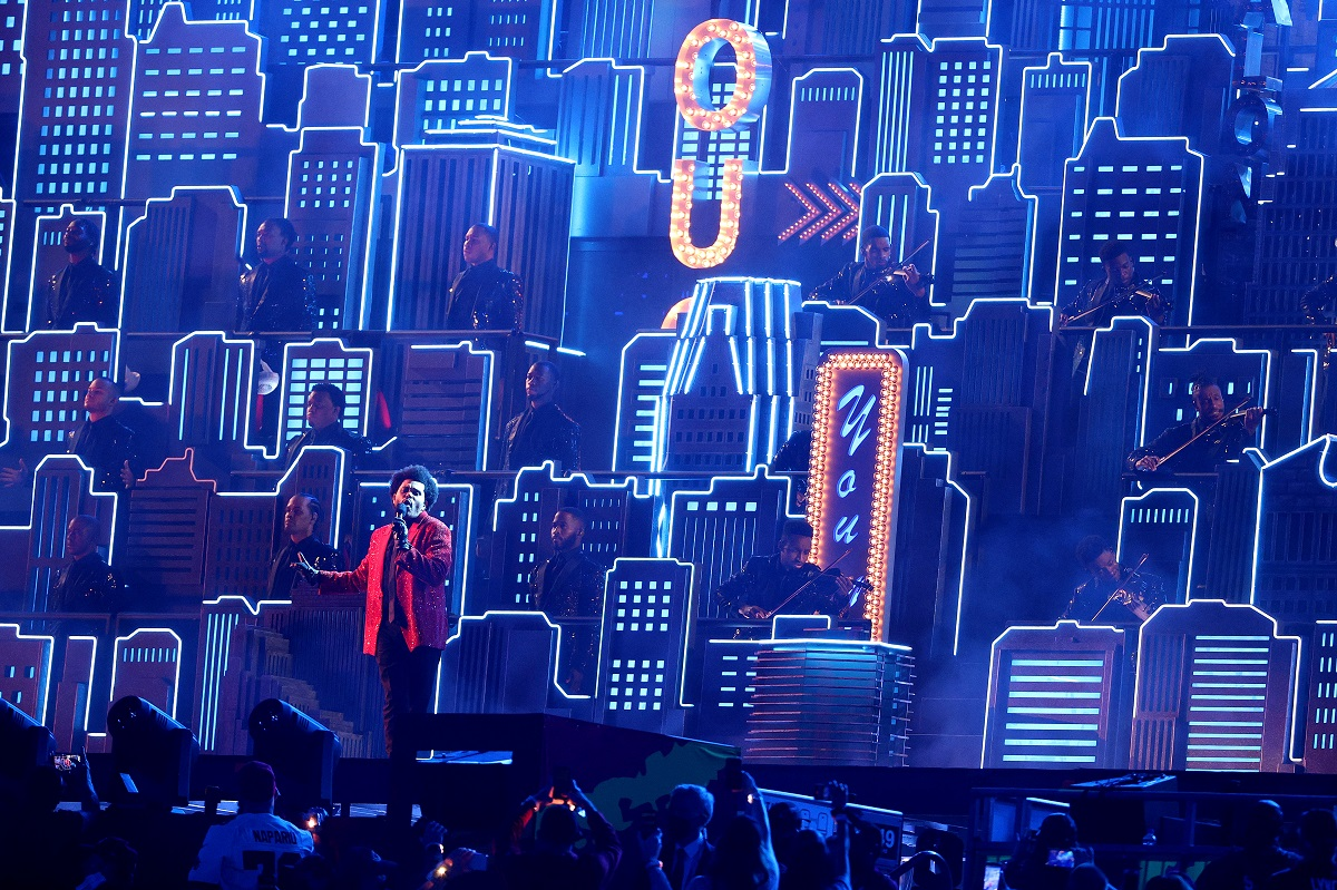 The Weeknd performing at the 2021 Super Bowl halftime show in front of a neon skyscraper backdrop