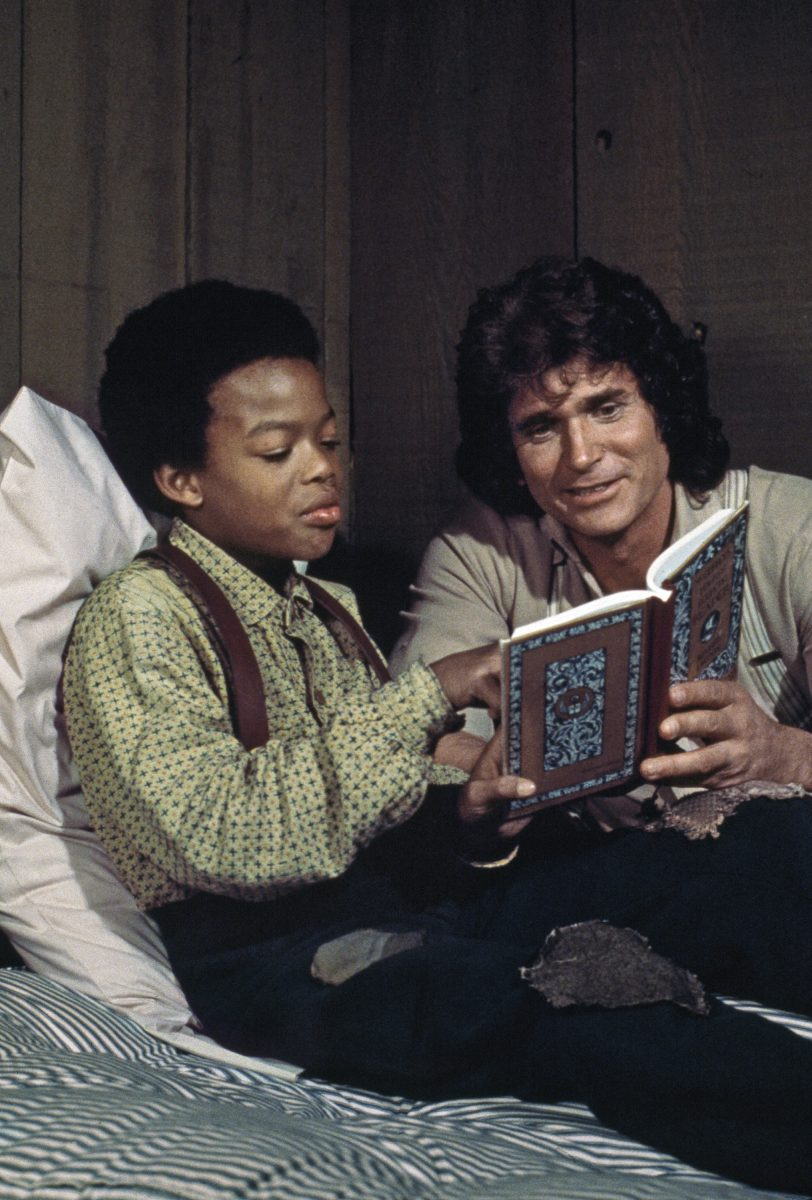 Michael Landon as Charles Ingalls reads a book to Todd Bridges as Solomon in an episode of Little House on the Prairie