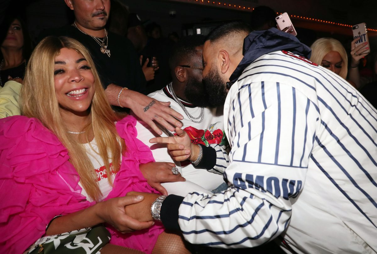 Wendy Williams smiling with a pink jacket and white t-shirt.