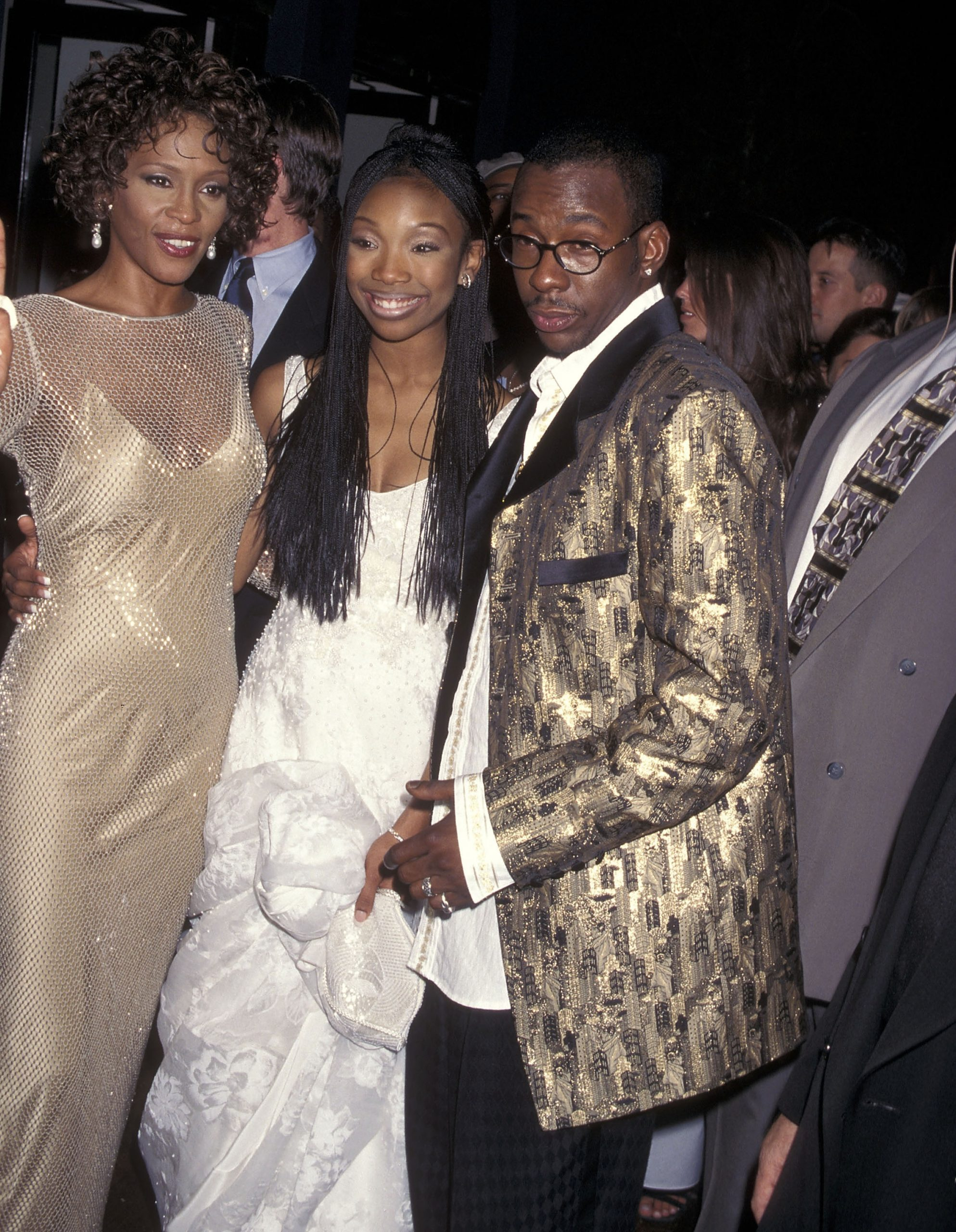 'Cinderella stars Whitney Houston in a gold dress and Brandy in a white dress. Bobby Brown in a black and gold blazer with glasses.