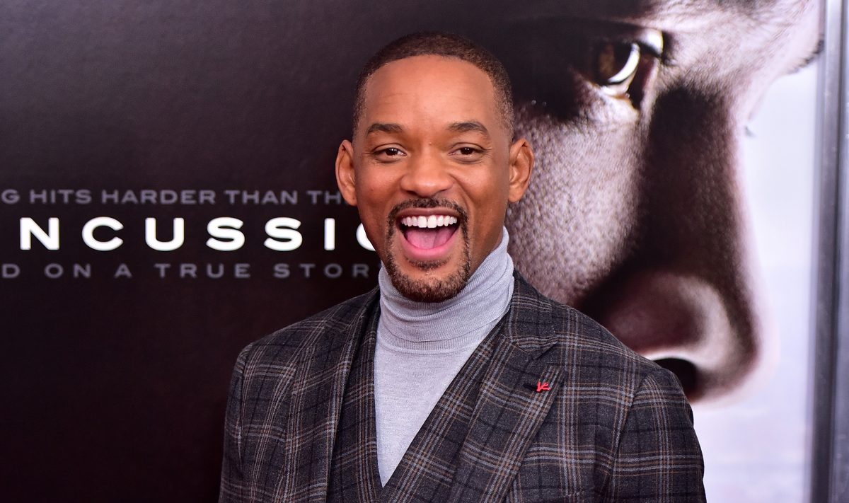 Will Smith smiling at a movie premiere wearing a grey turtleneck and plaid blazer.