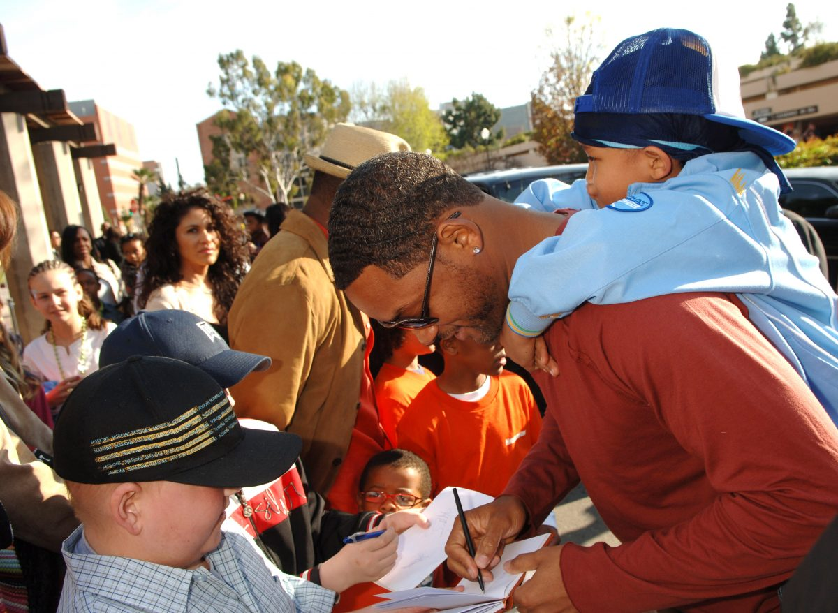 Will Smith signs autographs with Jaden on his shoulders