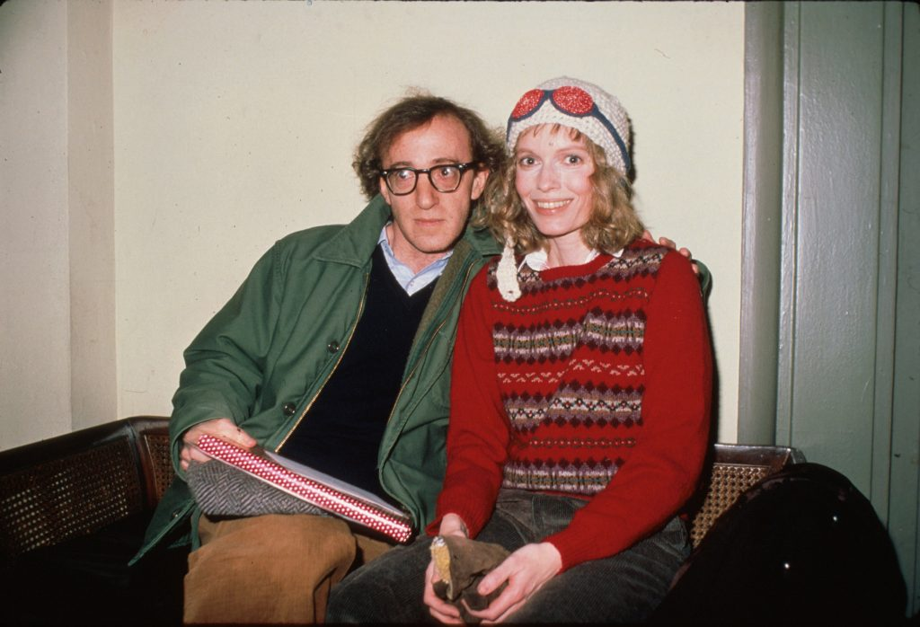 Woody Allen and Mia Farrow sitting together on a couch