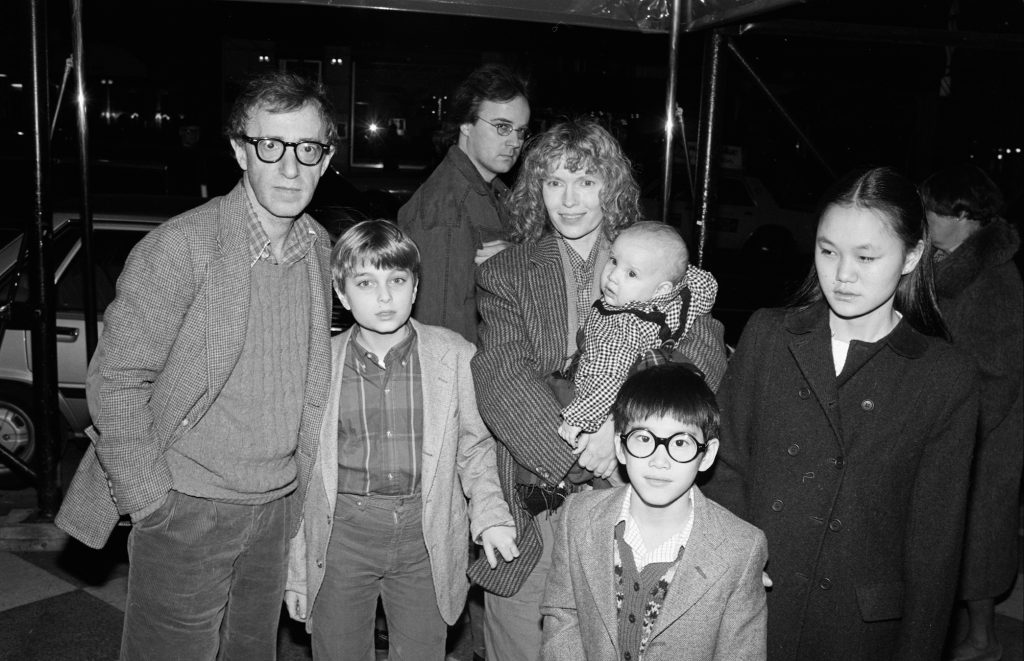 Woody Allen (left) and Mia Farrow pose under an awning with their children