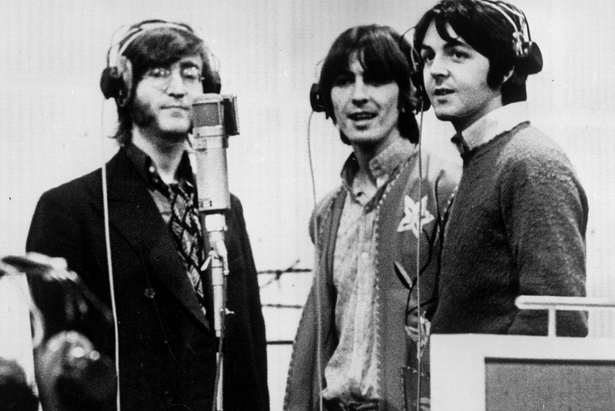 The Beatles standing around a microphone in a recording studio