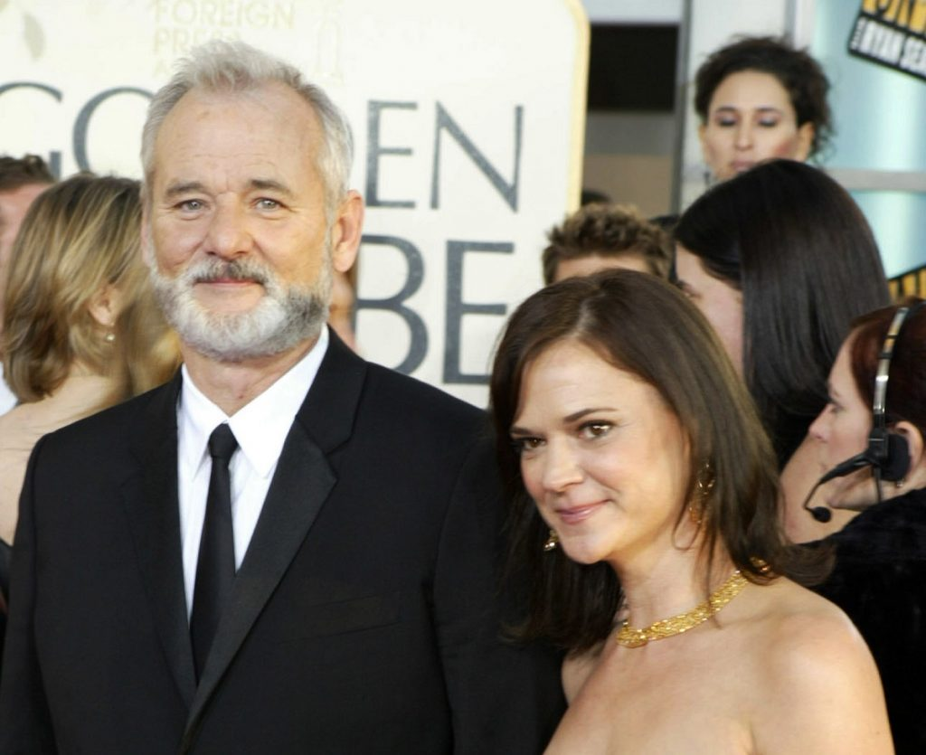 Bill Murray in a suit with his then-wife Jennifer Butler in front of a crowd