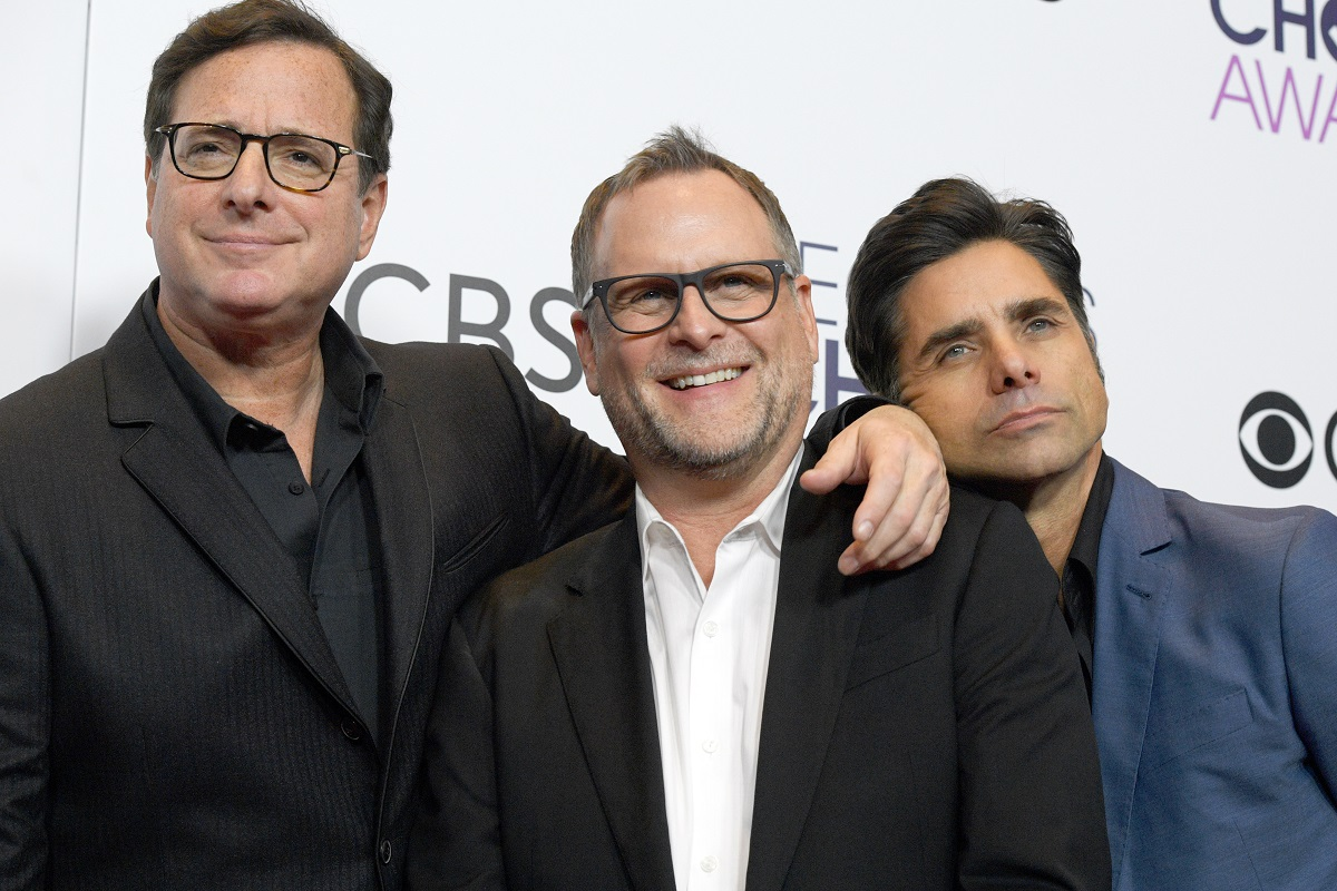 Bob Saget, Dave Coulier, and John Stamos pose with their arms around each other.