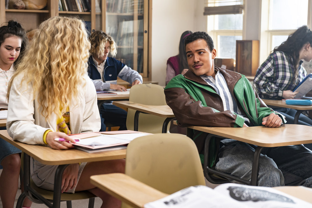 Bradley Constant as 15-year-old Dwayne Johnson talks to a blond girl with curly hair in a classroom