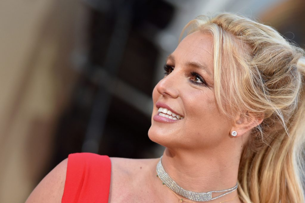 A head shot of Britney Spears smiling on the red carpet