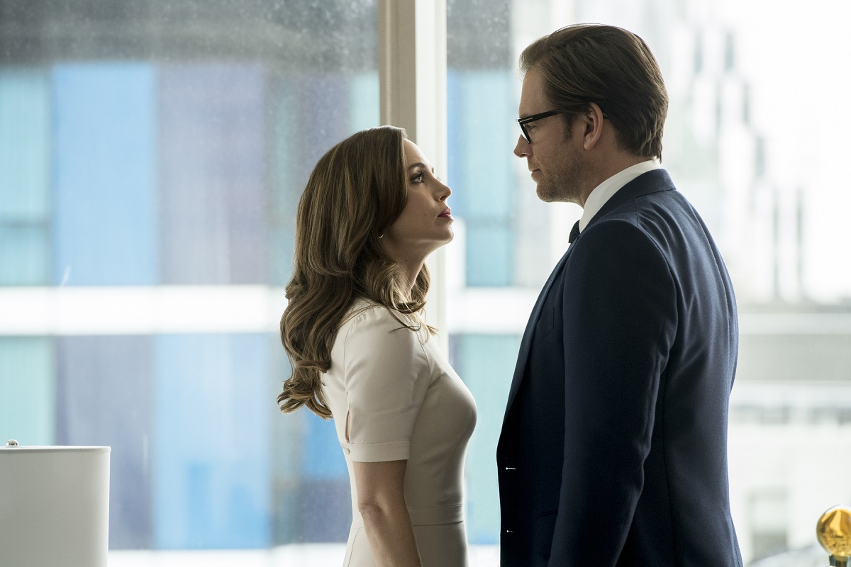 Eliza Dushku (L) and Michael Weatherly facce one another in front of an office window,